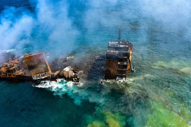 Smoke rises from a fire onboard the MV X-Press Pearl vessel as it sinks while being towed into deep sea off the Colombo Harbour, in Sri Lanka on June 2, 2021. The cargo ship, carrying tonnes of chemicals, sank off Sri Lanka's west coast after a fire raged on deck for two weeks, in one of the country's worst-ever marine disasters. (Photo by Sri Lanka Airforce Media/Handout via Reuters)