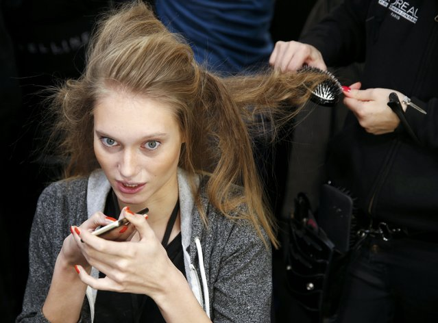 A model gets her hair done backstage for the presentation of the fashion label Anja Gockel at the Berlin Fashion Week Autumn/Winter 2016 in Berlin, Germany, January 20, 2016. (Photo by Fabrizio Bensch/Reuters)