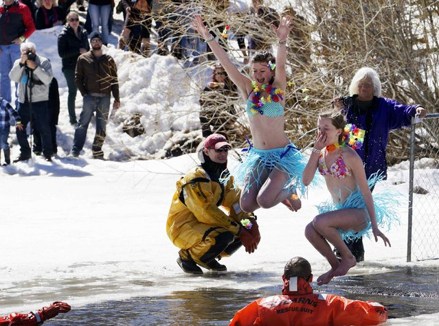 Two women jump into a frozen pond as they compete in the Polar Plunge at Frozen Dead Guy Days in Nederland, Colorado March 14, 2015. (Photo by Rick Wilking/Reuters)