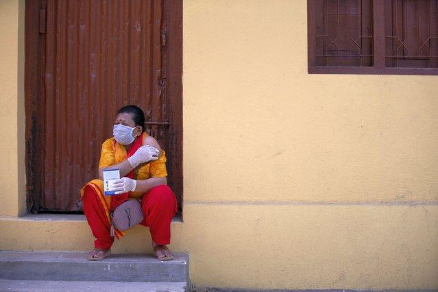 A Nepalese woman sits after getting inoculated against the coronavirus in Kathmandu, Nepal, Tuesday, June 8, 2021. (Photo by Bikram Rai/AP Photo)