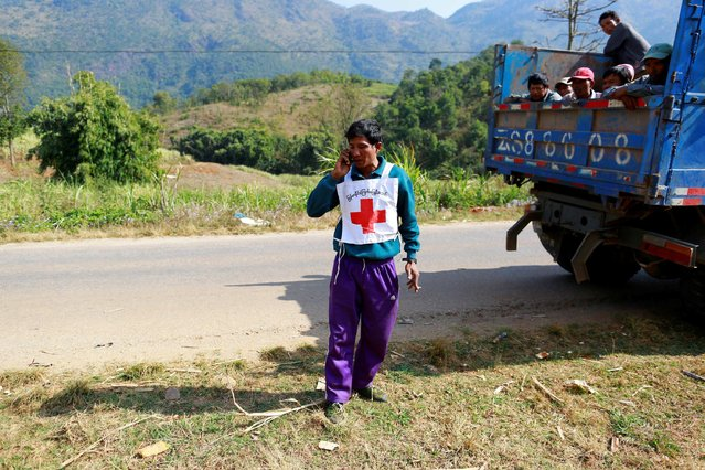 A volunteer driver of a Myanmar Red Cross Society rescue team convoy talks on the phone before he was wounded by unknown attackers, in Laukkai February 17, 2015. (Photo by Soe Zeya Tun/Reuters)