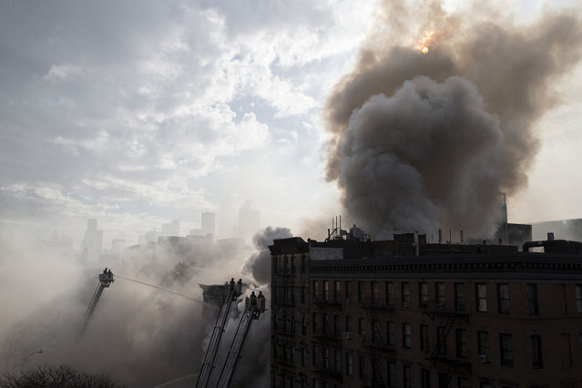 New York City firefighters work the scene of a large fire and a partial building collapse in the East Village neighborhood of New York on Thursday, March 26, 2015. Orange flames and black smoke are billowing from the facade and roof of the building near several New York University buildings. (Photo by John Minchillo/AP Photo)