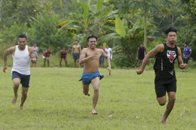 In this November 26, 2018 photo, men run during 100 meters athletics competition of the second edition of the Panamanian indigenous games in Piriati, Panama. These games were held in the Embera town of Piriati, some 55 miles (90 kilometers) east of Panama City. (Photo by Arnulfo Franco/AP Photo)