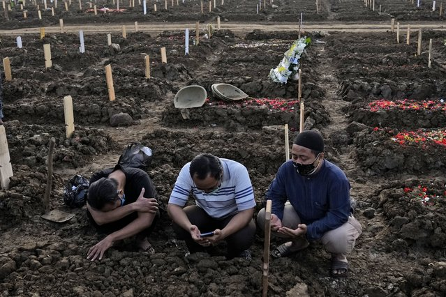 Men pray during the burial of a relative at Rorotan Cemetery which is reserved for those who died of COVID-19, in Jakarta, Indonesia, Thursday, July 1, 2021. New land around the capital city continues to be cleared for the dead and gravediggers have to work late shifts following surges in COVID-19 cases fueled by travel during the Eid holiday in May, and the spread of the delta variant of the coronavirus first found in India. (Photo by Dita Alangkara/AP Photo)