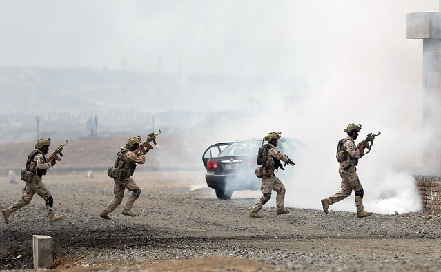 Afghanistan's interior ministry special forces take near a building during a military exercise in Kabul, Afghanistan, Thursday, April 2, 2015. (Photo by Massoud Hossaini/AP Photo)