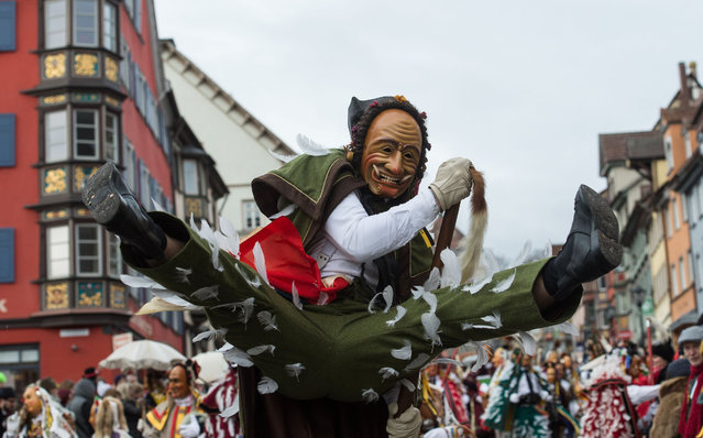 """A so-called """"Federhannes"""" carnival character jumps through the streets of Rottweil, southern Germany, during the """"Narrensprung"""" (Jump of the Fools) carnival parade on Rose Monday (Rosenmontag), February 8, 2016. (Photo by Patrick Seeger/AFP Photo/DPA)"""