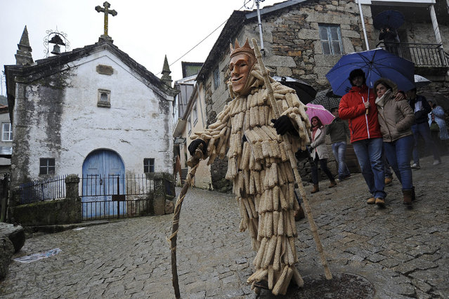 """A man dressed as a traditional """"careto"""" during the Lazarim carnival in Lamego, Portugal, 09 January 2016. """"Caretos"""" are a traditional celebration of the Portuguese carnival dating back to Celtic times where young men dress colorfull clothes, wooden masks and rattle belts to scare people on the streets specially single young girls. (Photo by Octavio Passos/EPA)"""