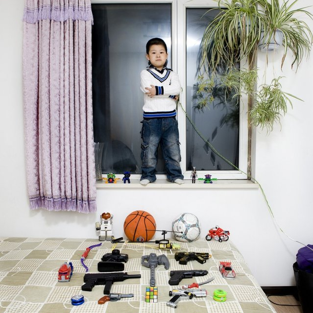 "Li Yi Chen – Shenyang, China. Li Yi was born in Shenyang, a big city in the north part of China. He lives with his parents and his grandmother in a small appartment in the south suburb of the city. His favourite toys are the guns. He loves to put little boxes above the table and then i likes to shoot at them rubbers bullets with the gun. He also love to play with the YoYo because his favourite character of cartoon uses the YoYo like a weapon. ""Toy Stories"" project. (Gabriele Galimberti)"