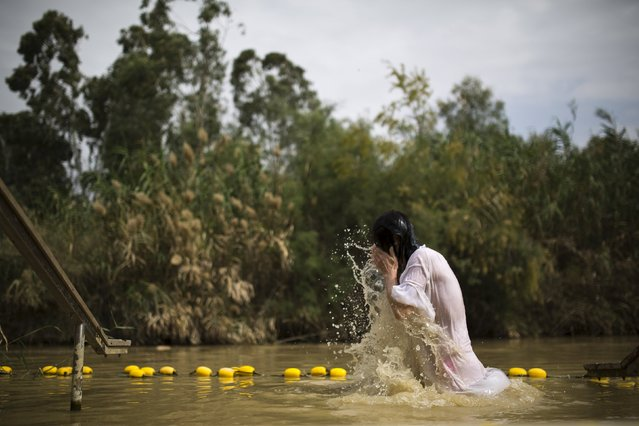 A Christian pilgrim dips in the water during his visit a day ahead of Orthodox Good Friday to the baptismal site known as Qasr el-Yahud on the banks of the Jordan River near the West Bank city of Jericho April 9, 2015. (Photo by Amir Cohen/Reuters)