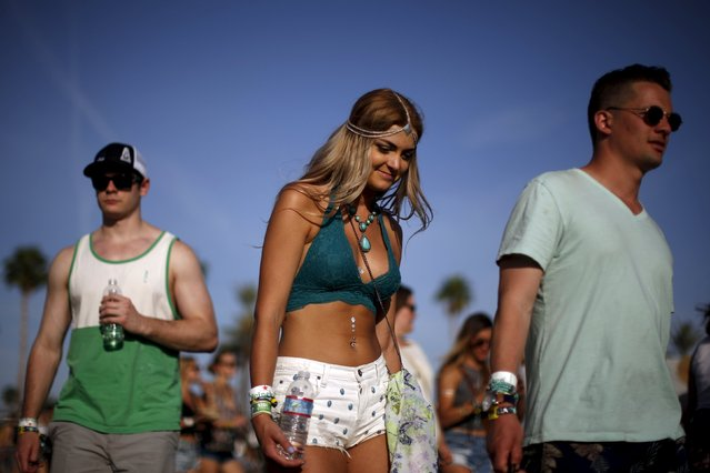 People walk through the Coachella Valley Music and Arts Festival in Indio, California April 10, 2015. (Photo by Lucy Nicholson/Reuters)