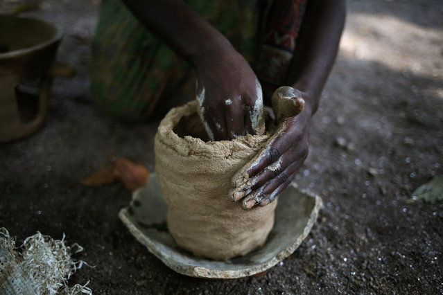 A woman makes a clay pot at Kagorwa Pygmy camp on Idjwi island in the Democratic Republic of Congo, November 23, 2016. (Photo by Therese Di Campo/Reuters)