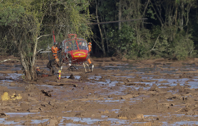 Rescue workers in a helicopter look for victims of a dam collapse in Brumadinho, Brazil, Sunday, January 27, 2019. A massive, deadly river of pale brown mud released by the collapse of a mining company dam on Friday threatens to cause an environmental disaster for Brazil, potentially snatching away livelihoods and driving the spread of disease, activists warned Sunday. (Photo by Andre Penner/AP Photo)