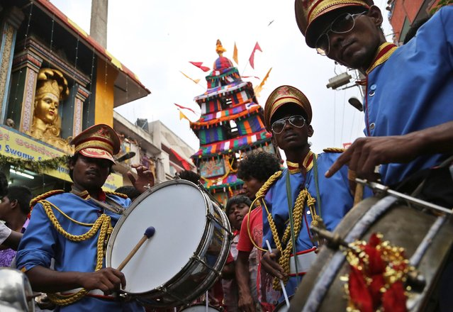 Members of a local brass band perform in front of a chariot carrying an idol of Hindu goddess Muthyalamma during the annual festival in her honor in Bangalore, India, Wednesday, April 1, 2015. The 16-day festival is one of the oldest continuously celebrated festivals of Bangalore. (Photo by Aijaz Rahi/AP Photo)