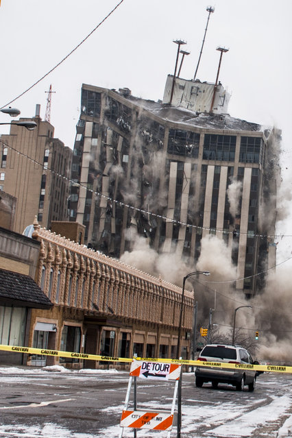 The Genesee Towers fall to the ground as explosives detonate for an implosion, Sunday, December 22, 2013 in downtown Flint, Mich. (Photo by Jake May/AP Photo/The Flint Journal)