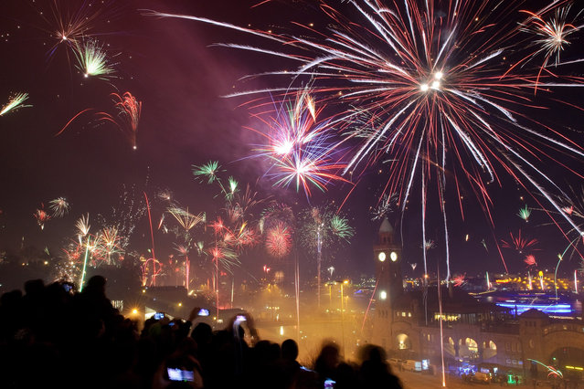 Thousands of people take part in the 2014 New Year celebrations as fireworks light the night sky in Hamburg, Germany, 01 January 2014. (Photo by Angelika Warmuth/EPA)
