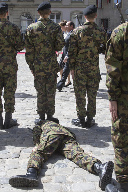 A member of the guard of honor lies on the ground while French President Francois Hollande, rear right, and his Swiss counterpart Simonetta Sommaruga inspect the guard of hounor in Bern, Switzerland, Wednesday, April 15, 2015. French President Francois Hollande is on a two-day official visit in Switzerland. (Peter Klaunzer/Keystone via AP Photo)