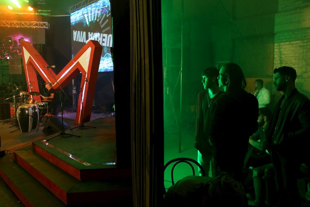 """Young people watch a rock presentation from the backstage of a cinema where the """"Cuerda Viva"""" (Live Strings) alternative music festival is taking place, in Havana, February 26, 2016. (Photo by Alexandre Meneghini/Reuters)"""