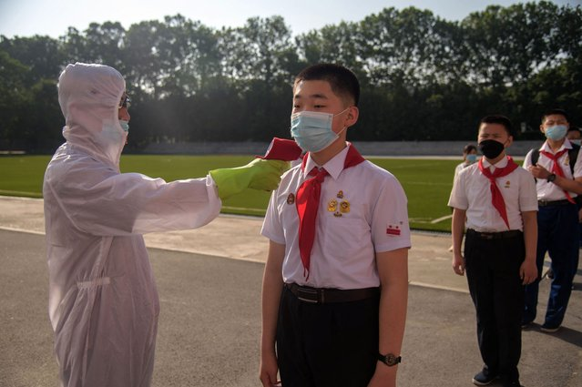 A pupil has his temperature taken as part of anti Covid-19 procedures before entering the Pyongyang Secondary School No. 1 in Pyongyang on June 22, 2021. (Photo by Kim Won Jin/AFP Photo)
