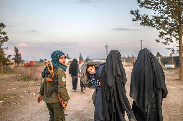 Veiled women, reportedly wives and members of the Islamic Stine, walk under the supervision of a female fighter from the Syrian Democrinic Forces (SDF) at al-Hol camp in al-Hasakeh governorate in northeastern Syria on February 17, 2019. (Photo by Bulent Kilic/AFP Photo)