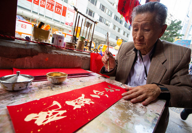 "A man paints Chinese New Year ""fai chun"" calligraphy couplets in gold paint as passersby crowd around him in the hope of buying one on the last day of the Chinese Year of the Dog, in Wan Chai, Hong Kong, China, 04 February 2019. Fai chun are usually placed on the front door of houses during the Chinese New Year period. The Chinese New Year of the Pig begins on 05 February 2019. (Photo by Alex Hofford/EPA/EFE)"