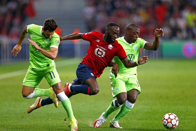 Lille's goalkeeper Ivo Grbic, center, is stopped by Wolfsburg's Renato Steffen, left, during the group G Champions League soccer match between Lille and Vfl Wolfsburg at the Stade Pierre Mauroy – Villeneuve d'Ascq stadium in Lille, France, Tuesday, September 14, 2021. (Photo by Michel Spingler/AP Photo)