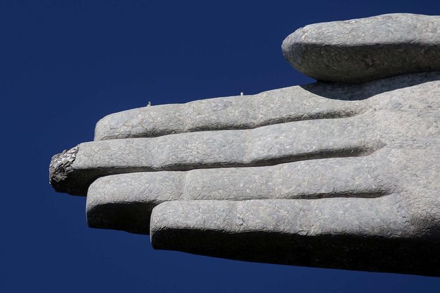 Seen on January 21, one of the fingers of the Christ Redeemer statue is chipped. The famed statue is being examined for repairs after two fingers and its head were chipped during recent lightning storms. Officials say they'll place more lightning rods on the statue in an effort to prevent future damage. (Photo by Felipe Dana/Associated Press)