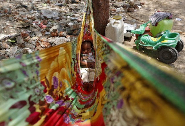 A child sleeps in a cloth hammock along a road in the western Indian city of Ahmedabad April 23, 2015. (Photo by Amit Dave/Reuters)