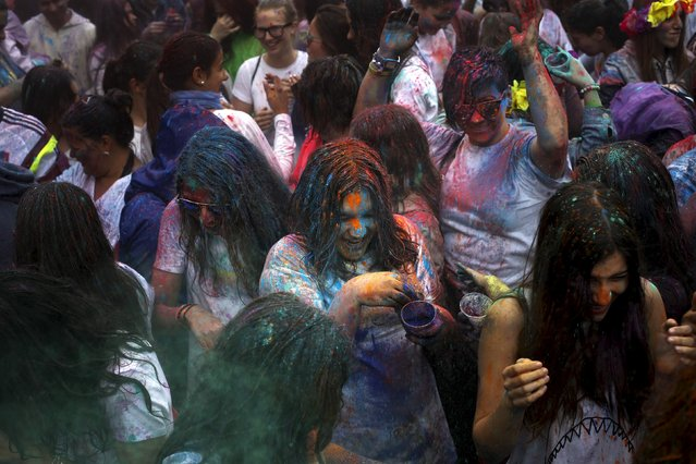 People throw coloured powder during Holi festival in Madrid April 26, 2015. Holi, also known as the Festival of Colours, heralds the beginning of spring and is celebrated all over India. (Photo by Susana Vera/Reuters)