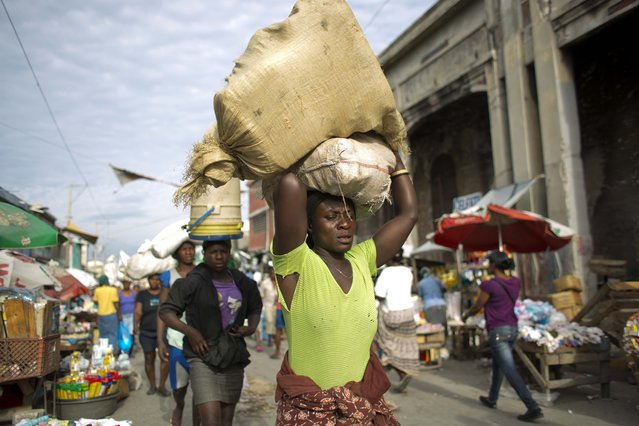 Women balance their staples on their heads as they make their way through the Croix-des-Bossales market in Port-au-Prince, Haiti, Tuesday, March 8, 2016. Tuesday marks International Women's Day, observed annually worldwide on March 8, celebrating women's achievements in all walks of life. (Photo by Dieu Nalio Chery/AP Photo)