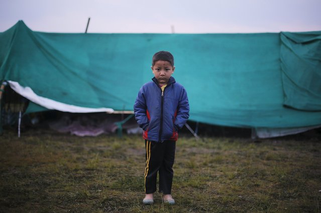 A boy stands outside his makeshift shelter at open ground in the early hours, after the April 25 earthquake in Kathmandu, Nepal April 29, 2015. (Photo by Adnan Abidi/Reuters)
