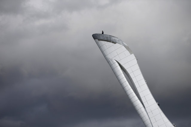 A worker is dwarfed against the sky as he stands at the top of the Olympic cauldron ahead of the 2014 Winter Olympics, Tuesday, February 4, 2014, in Sochi, Russia. (Photo by Wong Maye-E/AP Photo)