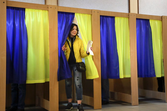 A woman holds her ballot before casting at a polling station during the presidential election in Kiev, Ukraine, Sunday, March 31, 2019. Ukrainians choose from among 39 candidates for a president they hope can guide the country of more than 42 million out of troubles including endemic corruption, a seemingly intractable conflict with Russia-backed separatists in the country's east and a struggling economy. (Photo by Sergei Grits/AP Photo)