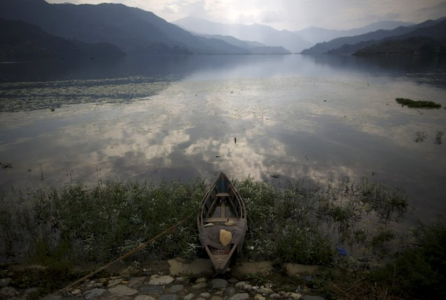 A boat lies on the banks of Phewa Lake in Pokhara, west of Nepal's capital Kathmandu June 29, 2015. Phewa, or Fewa, Lake is the second largest lake in Nepal. (Photo by Navesh Chitrakar/Reuters)