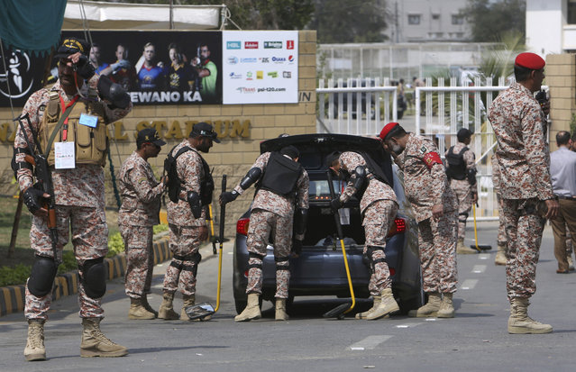 A Pakistani paramilitary soldier stands guard while others searching a car at the main entrance to National Stadium ahead of Pakistan Super League's cricket match in Karachi, Pakistan, Saturday, March 9, 2019. Pakistan's biggest city is set to witness some of the biggest stars in international cricket over the next nine days as the last leg of Pakistan Super League begins on Saturday. (Photo by Fareed Khan/AP Photo)