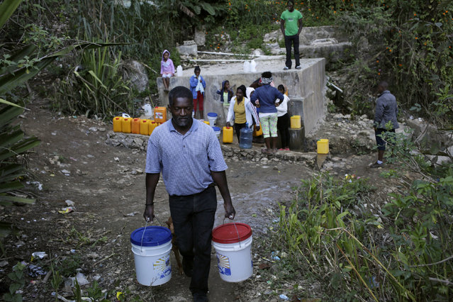 Andre Louis Jean carries two buckets of water at a fountain in the outskirts of Kenscoff, Haiti, February 23, 2016. March 22 marks World Water Day. (Photo by Andres Martinez Casares/Reuters)