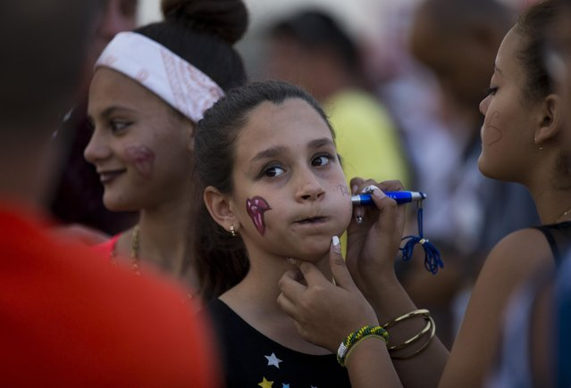 A girl has the words Rolling Stones written on her face before their concert at the Ciudad Deportiva in Havana, Cuba, Friday March 25, 2016. The Stones performed a free concert in Havana, becoming the most famous act to play Cuba since its 1959 revolution. (Photo by Ismael Francisco/Cubadebate via AP Photo)