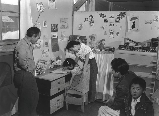 Toyo Miyatake stands in his children's bedroom looking at his young daughter drawing at a desk, while her mother stands behind her, at the Manzanar War Relocation Center in California, in this 1943 handout photo. (Photo by Courtesy Ansel Adams/Library of Congress, Prints and Photographs Division/Reuters)