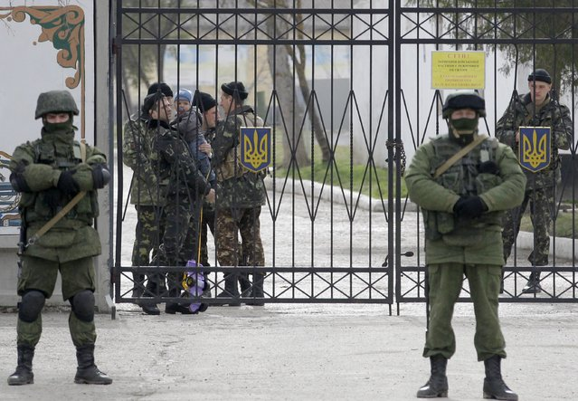 A Ukrainian soldier with a childm 2nd left, watches Russian soldier guard the gate of an infantry base in Perevalne, Ukraine, Tuesday, March 4, 2014. (Photo by Darko Vojinovic/AP Photo)