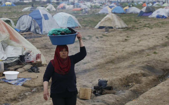 A woman walks through the makeshift refugee camp at the northern Greek border point of Idomeni, Greece, Monday, March 28, 2016. Over 11,000 refugees and migrants stranded at this makeshift encampment, some for weeks, after Balkan countries on what used to be the busiest migrant route to central and northern Europe shut down their borders. (Photo by Darko Vojinovic/AP Photo)