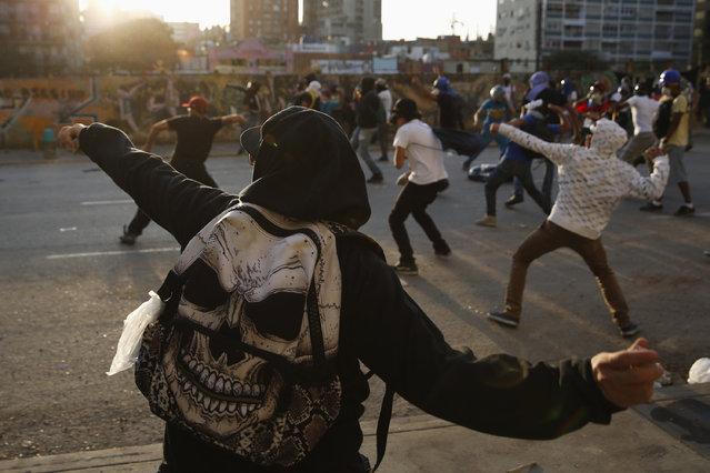 Anti-government protesters throw stones at riot police during a protest against Nicolas Maduro's government in Caracas March 5, 2014. Followers of late socialist leader Hugo Chavez flooded the streets of Venezuela on Wednesday for the anniversary of his death, an emotional but welcome distraction for his successor from violent protests raging for the last month. (Photo by Carlos Garcia Rawlins/Reuters)