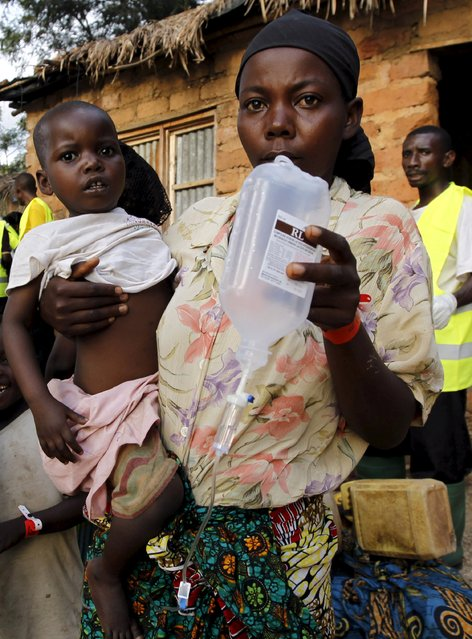 A Burundian refugee carries her sick child as she receives treatment at a makeshift clinic on the shores of Lake Tanganyika in Kagunga village in Kigoma region in western Tanzania, as they wait for MV Liemba to transport them to Kigoma township, May 17, 2015. (Photo by Thomas Mukoya/Reuters)