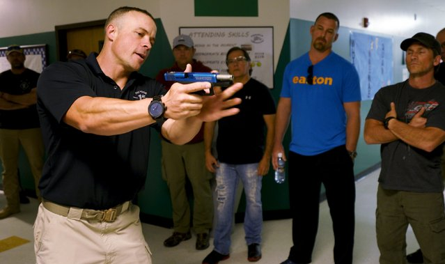 Joe Deedon, president of TAC ONE Consulting, demonstrates proper grip of a pistol prior to showing how to search for a shooter in a middle school during an Active Shooter Response course offered by TAC ONE in Denver April 2, 2016. (Photo by Rick Wilking/Reuters)