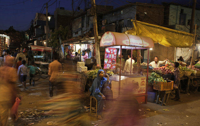 A roadside ice-cream vendor waits for customers at a market in New Delhi, India, April 7, 2016. The Indian economy is characterized by the existence of a vast majority of informal or unorganized labor employment. (Photo by Altaf Qadri/AP Photo)