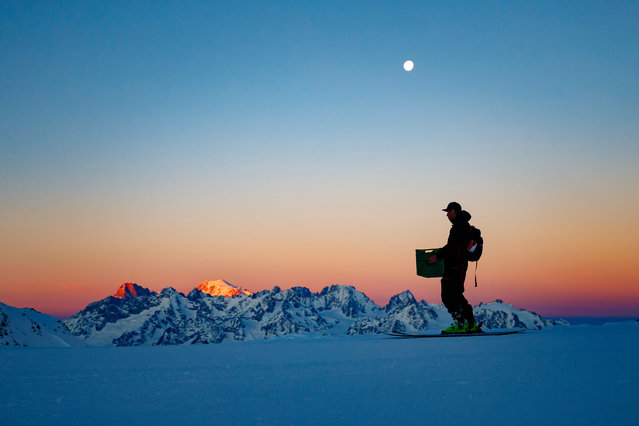 """A man carries equipment as the sun rises on the Mont Blanc mountain prior to the Verbier Xtreme Freeride World Tour (FWT) finals on the """"Bec des Rosses"""" mountain above the alpine resort of Verbier, Switzerland, Saturday, March 23, 2019. (Photo by Valentin Flauraud/EPA/EFE)"""
