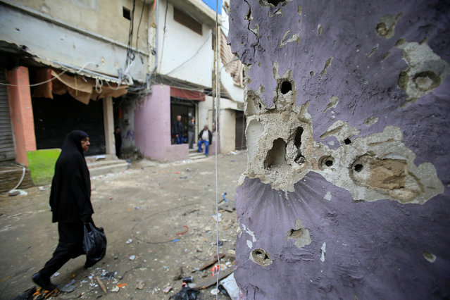 A woman walks past a bullet-riddled wall in the Ain el-Hilweh Palestinian refugee camp in southern Lebanon, March 1, 2017. (Photo by Ali Hashisho/Reuters)