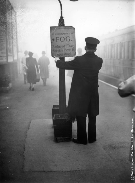 1938: A rail worker fixing a fog warning notice at South Woodford Railway Station in Essex