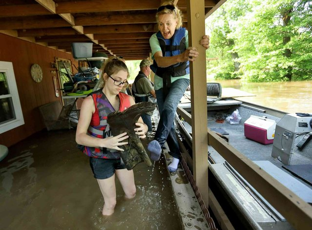 Emily Kientzel empties the water out of her grandmother Joan FitzGerald's boot that filled with floodwater from the Mississippi River, as they check on the home of a friend outside of Portage des Sioux, Mo., Sunday, June 2, 2019. The pair are standing on the second story balcony of the home that has more than a foot of water in it. (Photo by David Carson/St. Louis Post-Dispatch via AP Photo)