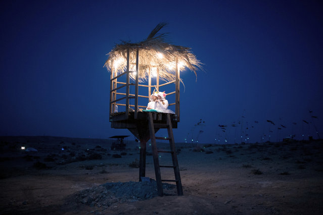 A couple dressed in costumes sit inside a hut during the 2015 Midburn festival in the Negev Desert near the Israeli kibbutz of Sde Boker on May 21, 2015. Some 6000 Israelis and foreigners attended the five days of the Midburn festival, the Israeli version of the popular Burning Man festival held annually in the Black Rock Desert of Nevada. (Photo by Menahem Kahana/AFP Photo)