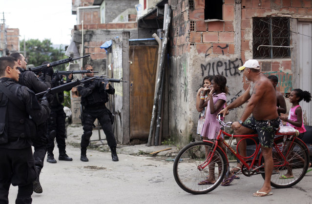 Residents react as policemen take position during an operation in the Mare slums complex in Rio de Janeiro March 26, 2014. Brazil will deploy federal troops to Rio de Janeiro to help quell a surge in violent crime following attacks by drug traffickers on police posts in three slums on the north side of the city, government officials said on Friday. (Photo by Ricardo Moraes/Reuters)