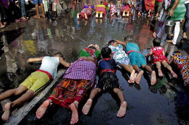 Hindu devotees move in a prostrating position as part of rituals on Sitala Puja, dedicated to the Hindu goddess of pox, in Kolkata, India, Saturday, April 16, 2016. Devotees participate to various rituals during this event to make a wish for the well being of their family. (Photo by Bikas Das/AP Photo)